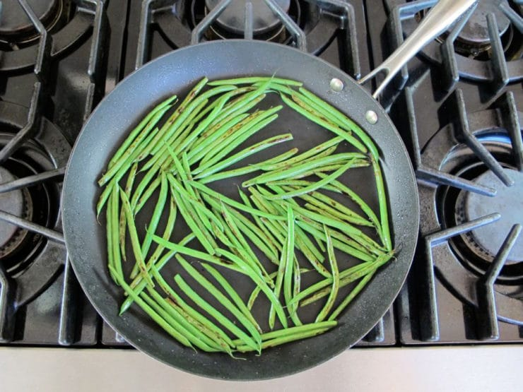 Sauteeing green beans in a skillet.
