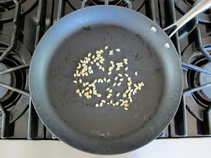 Toasting pine nuts in a skillet.