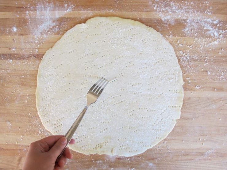 Using a fork to poke holes in a pizza crust.