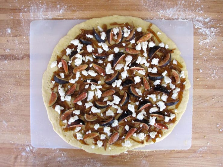 Raw pizza crust topped with caramelized onions and figs.