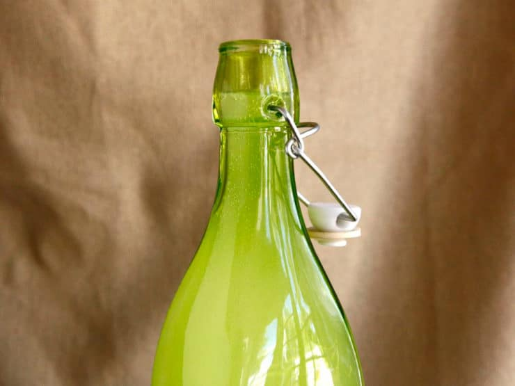 Fizzy ginger beer in green glass bottle, close up.