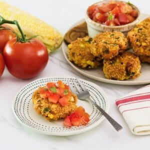 Horizontal shot of panko corn and pepper schnitzel, topped with tomato relish on a small plate with a fork. In the background there is a plate to the right with more schnitzel and relish, to the left there are whole tomatoes.