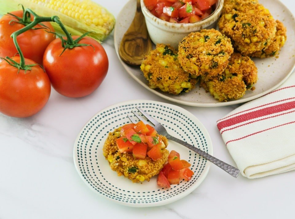 Horizontal angled overhead shot of panko corn and pepper schnitzel, topped with tomato relish on a small plate with a fork. In the background there is a plate to the right with more schnitzel and relish, to the left there are whole tomatoes.