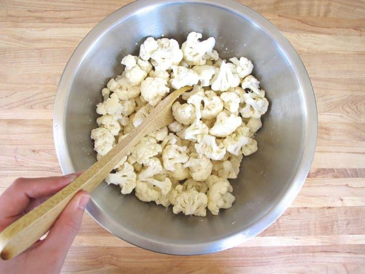 Stirring kosher salt into pieced cauliflower.