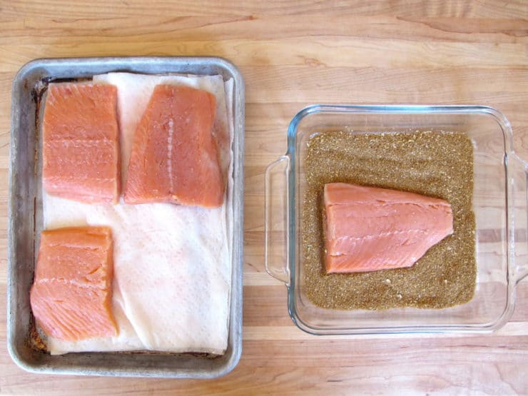 Salmon fillets on a lined baking sheet.