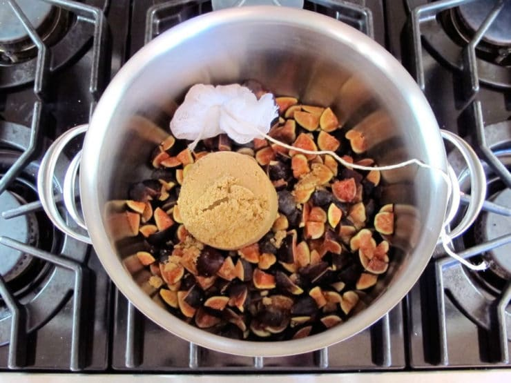 Spices and figs in a stock pot.