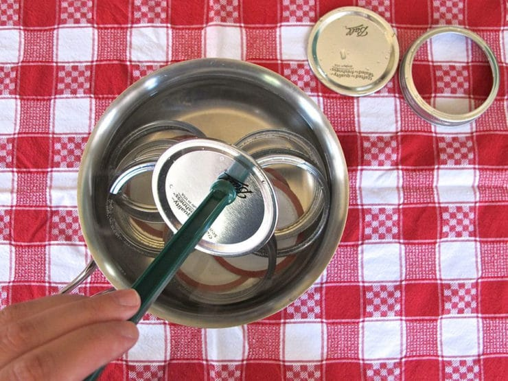 Using tongs to remove sterile lids from simmer water, red checked towel in background.