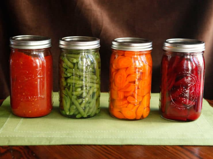 Four jars in a line, filled with canned colorful vegetables - green beans, beets, carrots and tomato sauce on a green placemat.