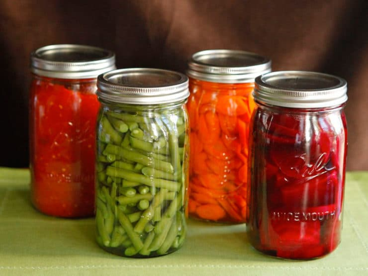 Four jars staggered, filled with canned colorful vegetables - green beans, beets, carrots and tomato sauce on a green placemat.