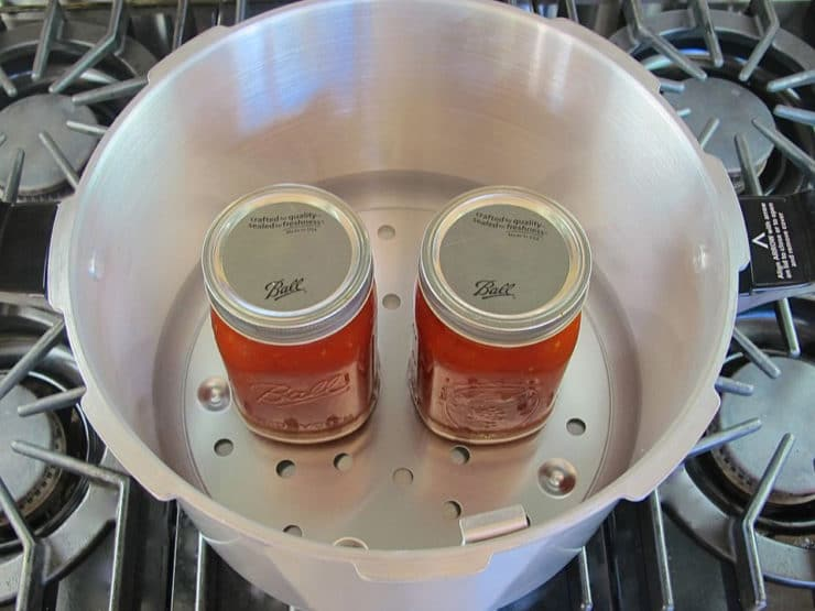 Two jars on canning rack in canner on stovetop.