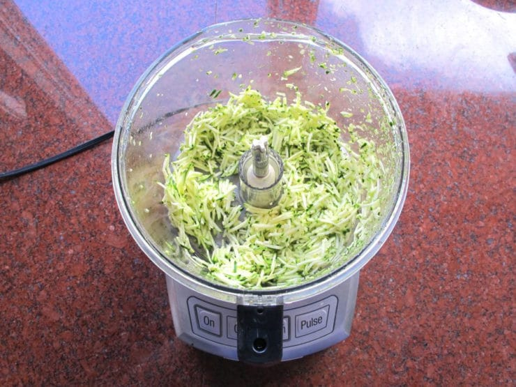Grating zucchini in a food processor.