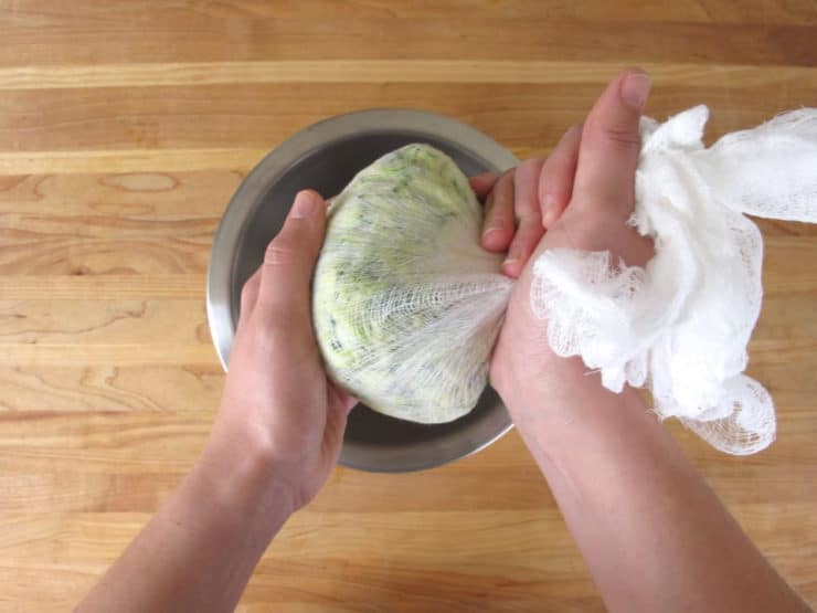Wrapping shredded vegetables in cheesecloth for straining.