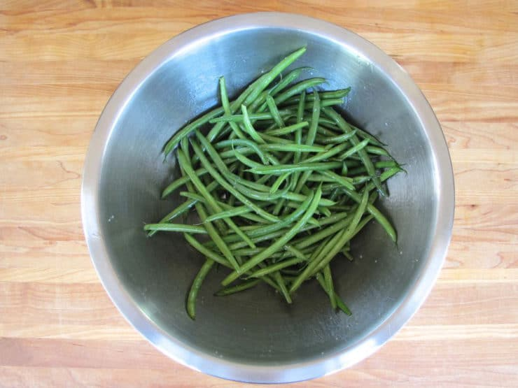 Green beans in a large mixing bowl tossed with oil and seasonings.