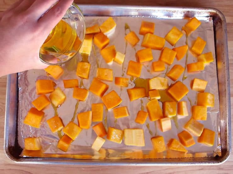 Drizzling oil over cubed butternut squash.