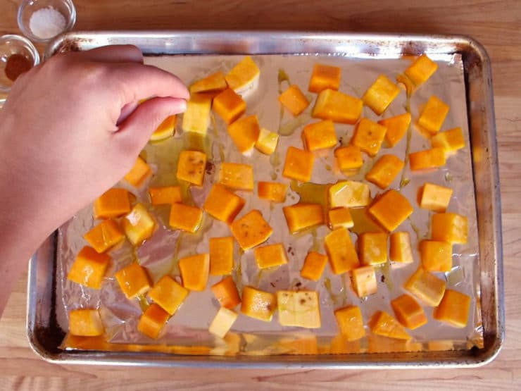 Sprinkling salt over cubed butternut squash.