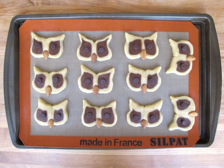 Owl cookies on lined baking sheet.
