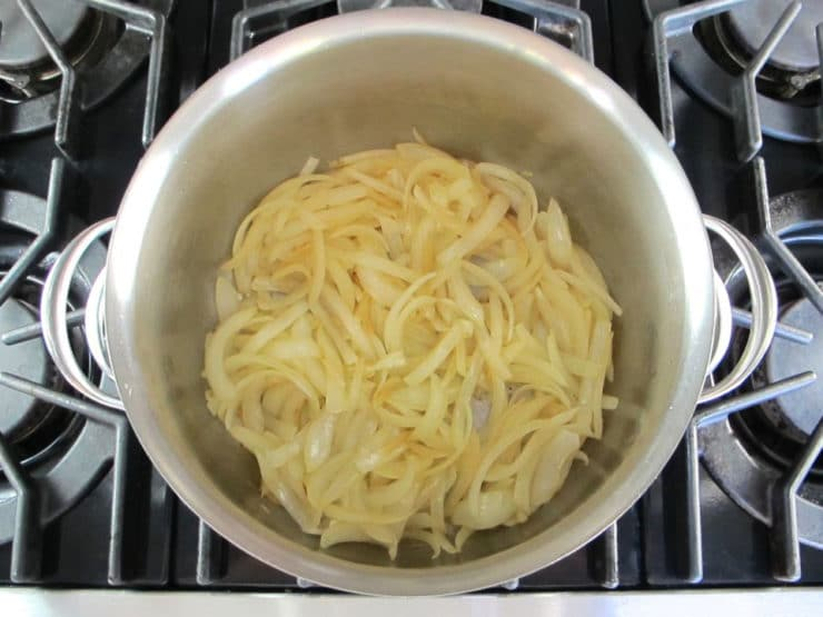 Sliced onions in a stockpot.
