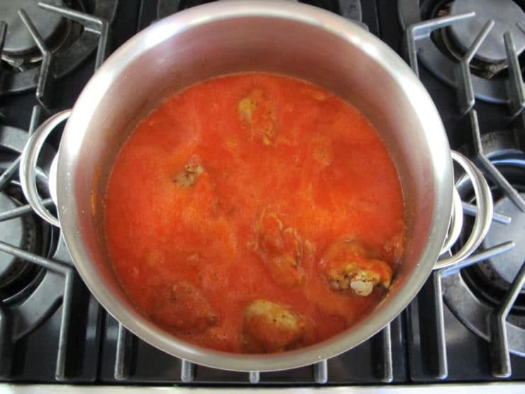 Paprikash sauce poured over chicken pieces in stockpot.