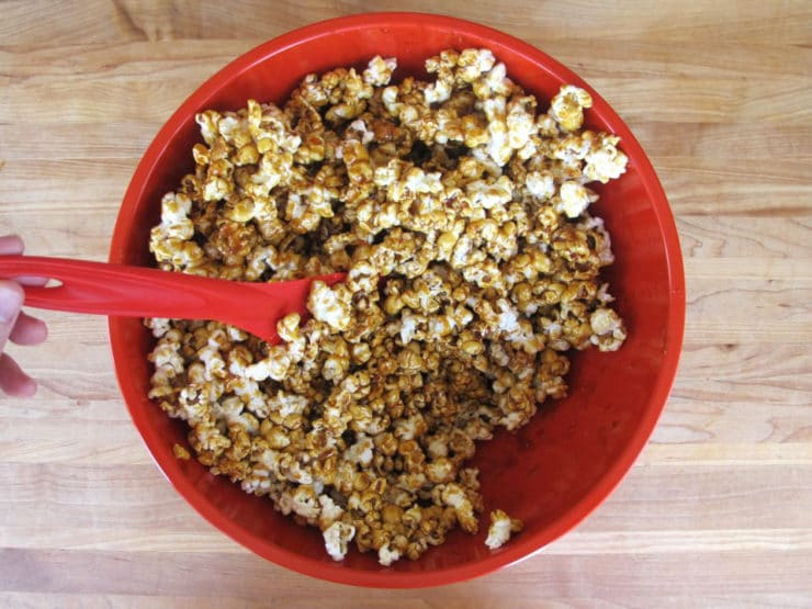 Gently stirring syrup into popcorn.