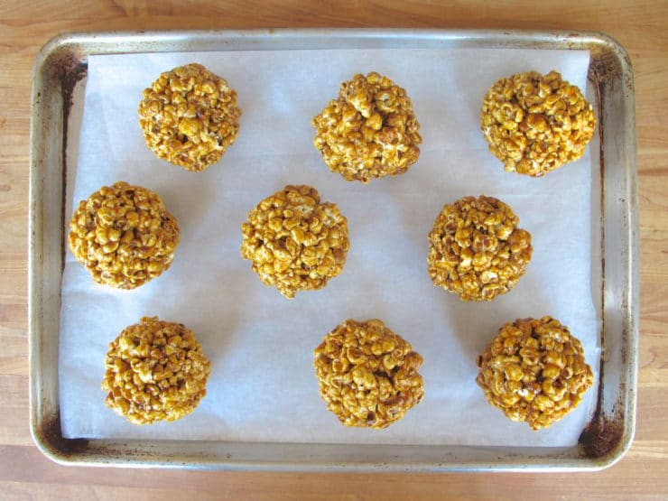 Popcorn balls on a lined baking sheet. to dry.