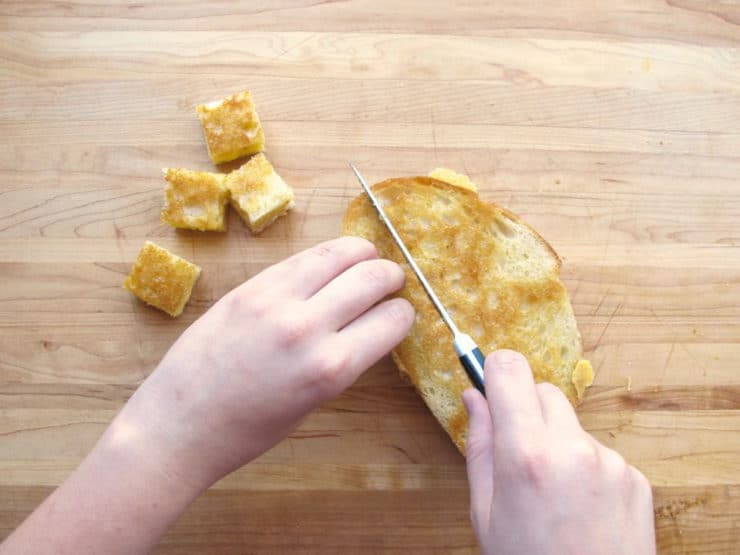 Cubing grilled cheese sandwiches for croutons.