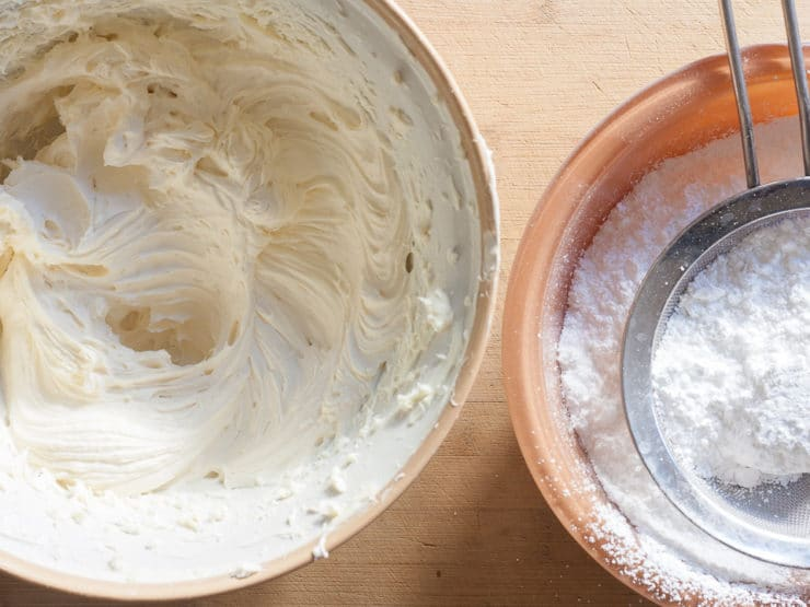 Gradually adding sugar to cream cheese frosting.