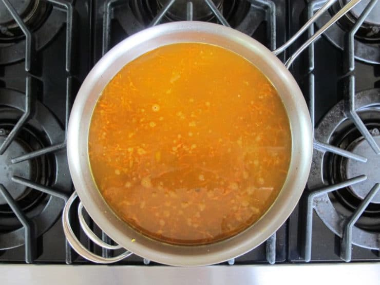 Simmer stock and vegetables until sauce is bright orange.