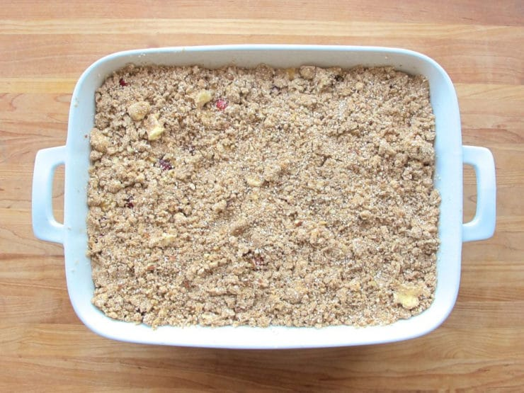 Matzo crisp topping spread over fruit filling in a baking dish.