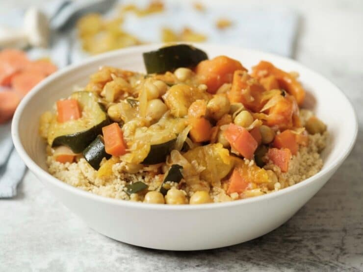Close up horizontal shot - white dish of vegetable couscous with chickpeas, carrots, and zucchini on white marble background with towel, dry ingredients in backround - garlic, apricots, raisins.