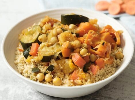 Square crop - dish of vegetable couscous on white marble background with towel, dry ingredients in backround - garlic, apricots, raisins.