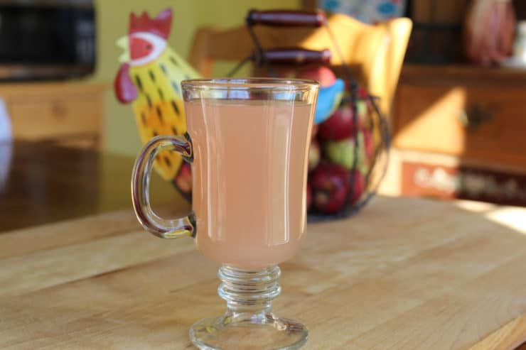 Homemade apple juice in a large glass.
