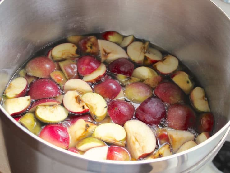 Quartered apples in a large stockpot of water.