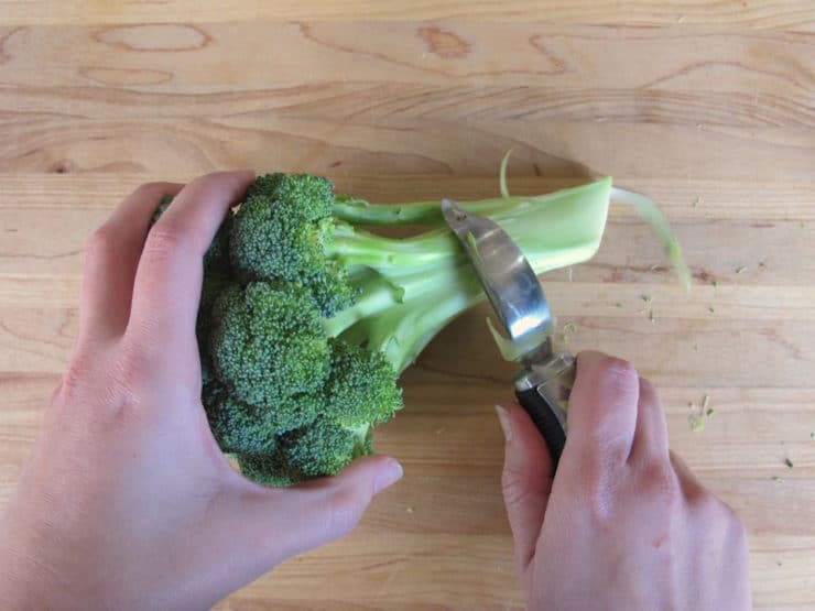 Peeling the outer part of broccoli stems.