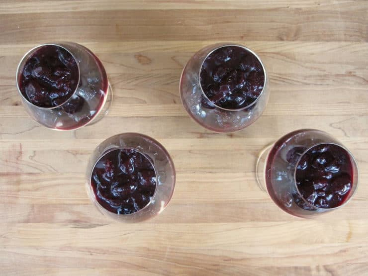Adding cherry filling on top of cheesecake in glasses.