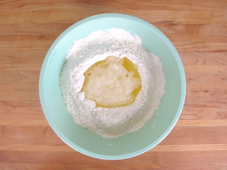 Stirring egg whites into powdered sugar.