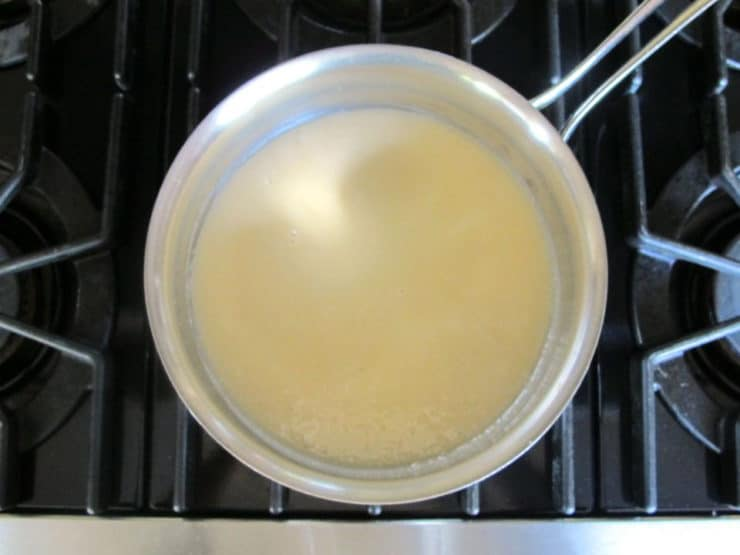 Gently heating egg whites and sugar.