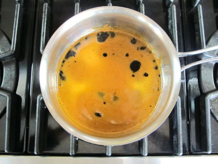 Heating molasses in a saucepan.
