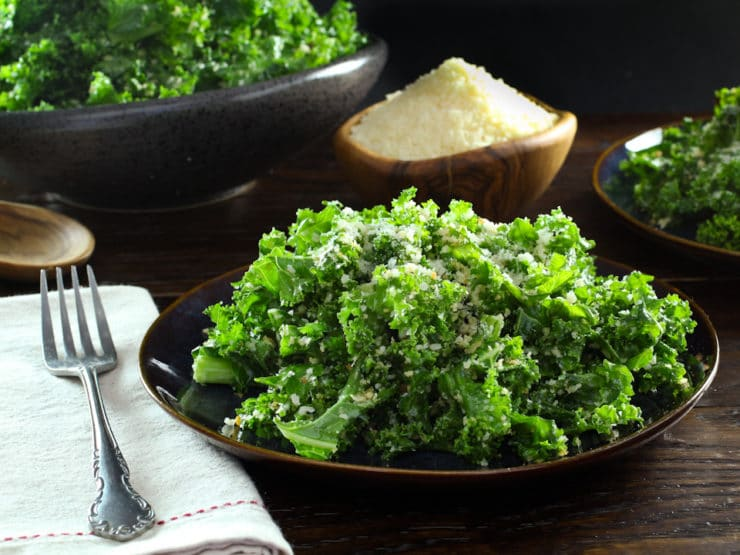 Garlicky Kale, Parmesan and Panko salad on a plate next to a fork sitting on top of white napkin, in the background is a bowl of grated parmesan cheese and a bowl of kale.
