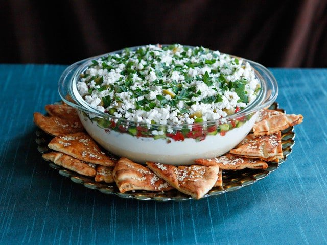 Mediterranean 7 Layer Dip - A healthy Mediterranean twist on seven layer dip with hummus, Greek yogurt, Greek olives, feta cheese and more. Serve with pita chips or crudités.