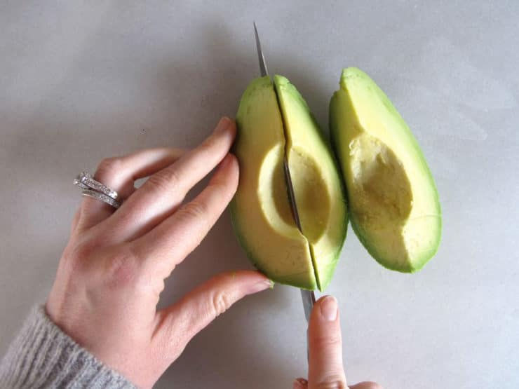 Slicing peeled avocado.