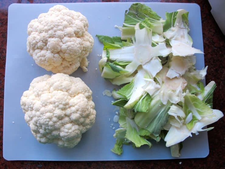 Stem and leaves removed from cauliflower heads.