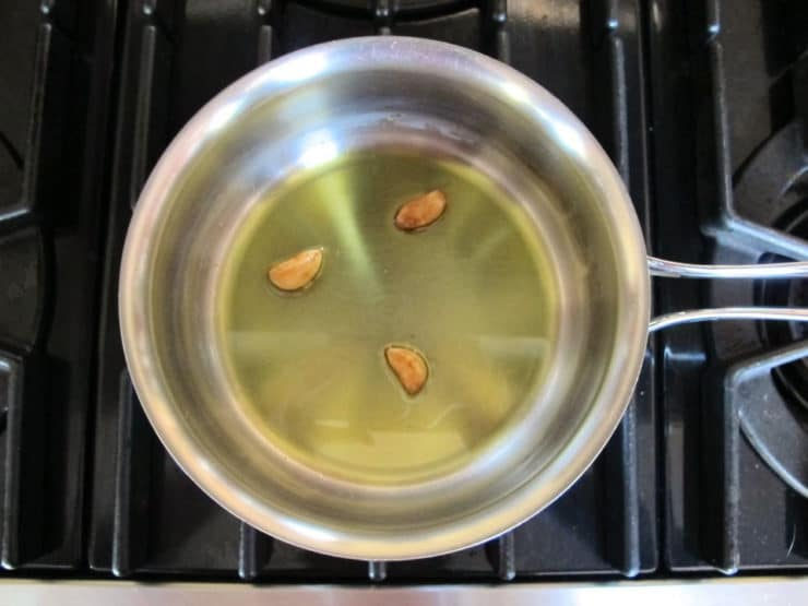 Roasting garlic cloves in oil.