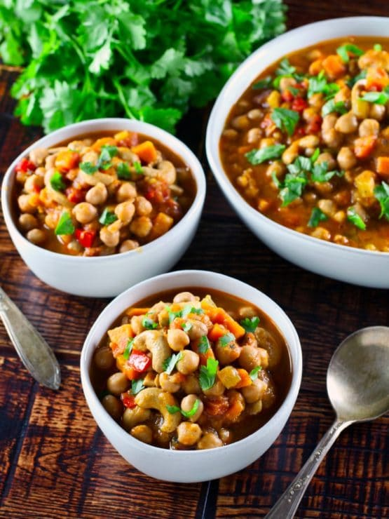 Vertical shot of two bowls of vegan chickpea chili with spoon and larger serving bowl of chili on wooden background, fresh cilantro in background.