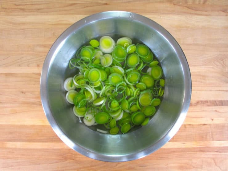 Sliced leeks submerged in a bowl of water.