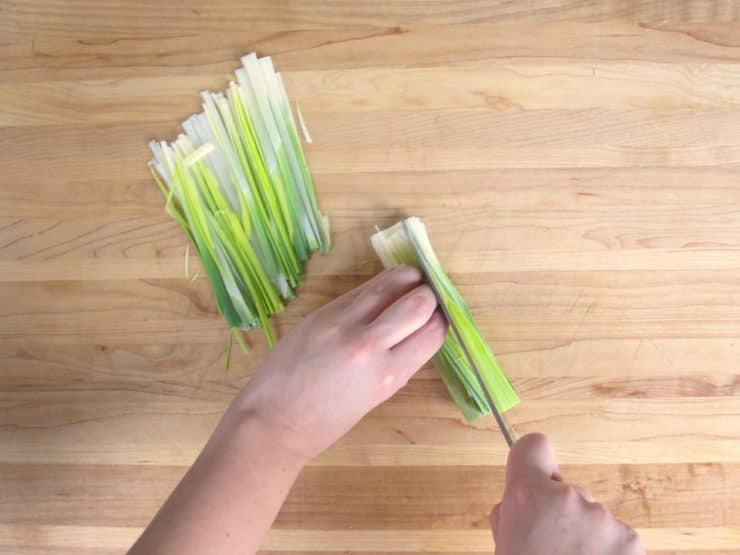 Slicing leeks into thin strips.