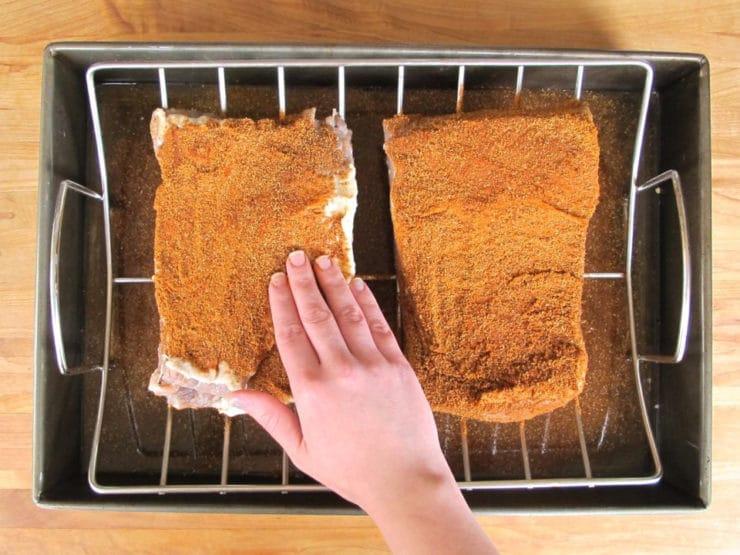 Rubbing spices on brisket.
