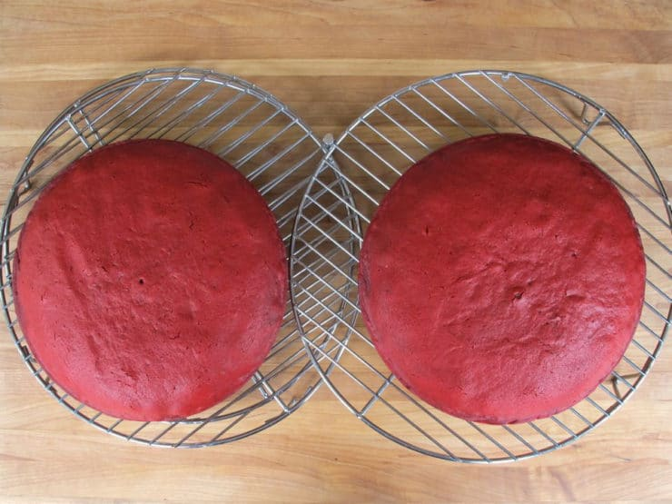 Two round cake layers cooling on a rack.
