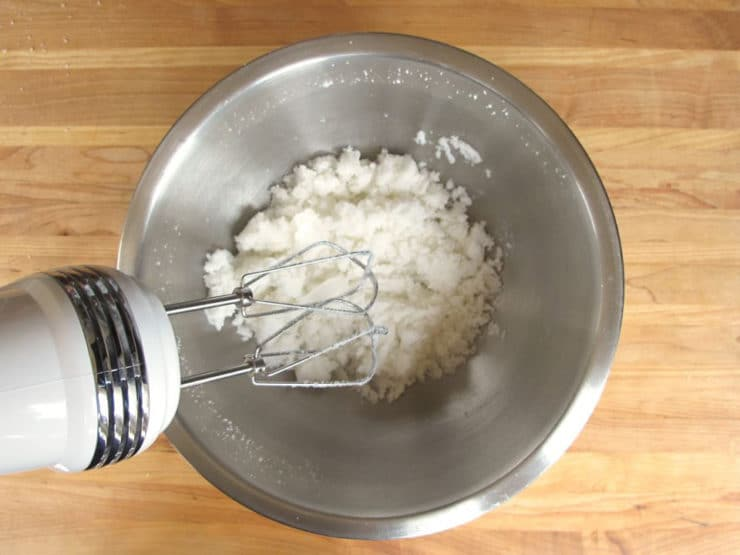 Creaming shortening and sugar with a mixer.