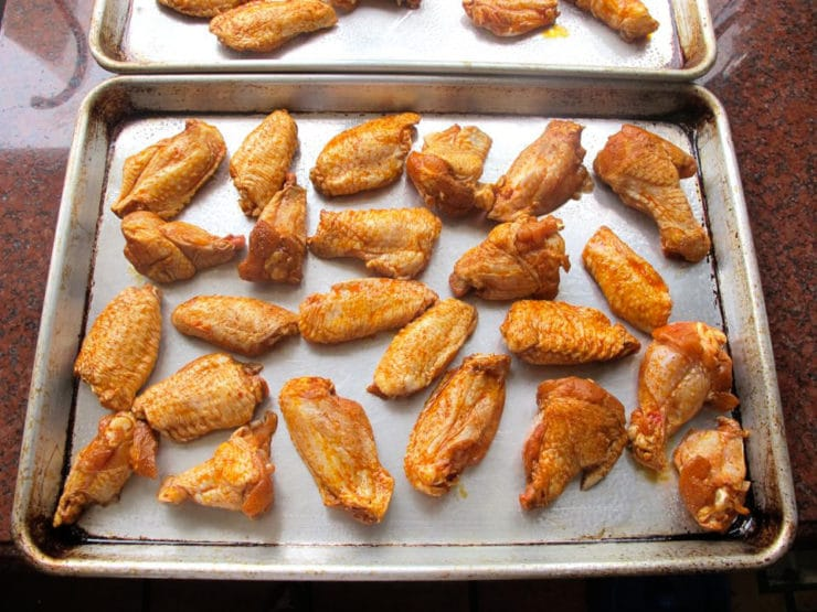 Marinated chicken wings spread out on a baking sheet.