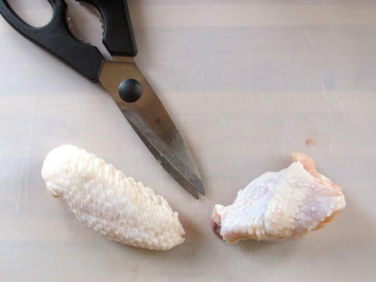 Separating the two chicken wing parts.